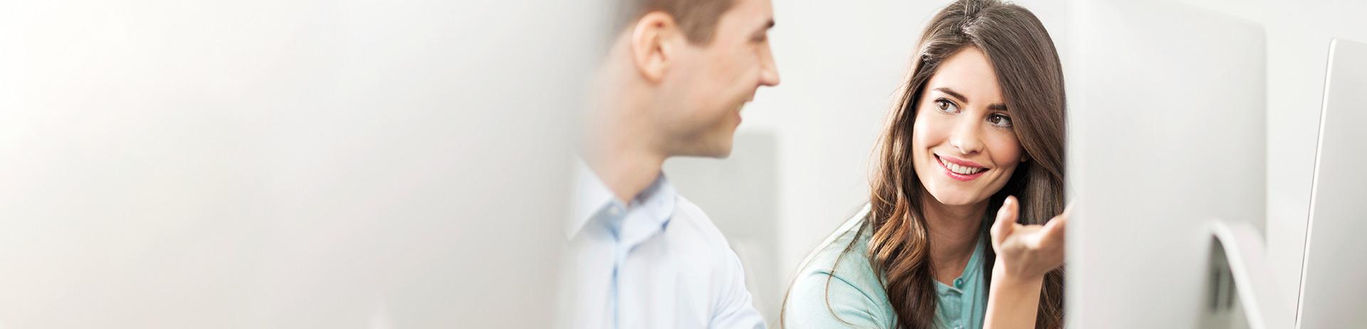 eine junge Dame und ein junger Herr sitzen vor einem Bildschirm