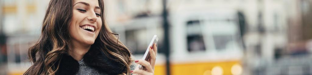 Frau, die sich über eine Nachricht auf ihrem Handy freut