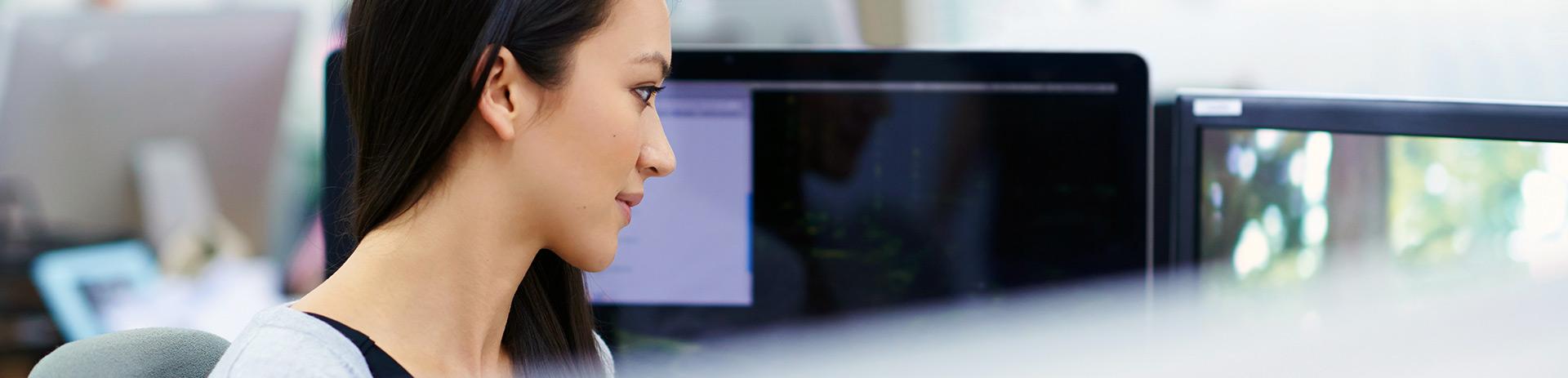 eine junge Frau sitzt vor zwei Bildschirmen