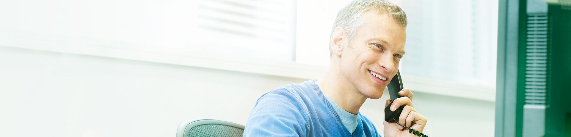 Mann im legeren Businessoutfit sitzt an seinem Schreibtisch und telefoniert mit dem Festnetztelefon