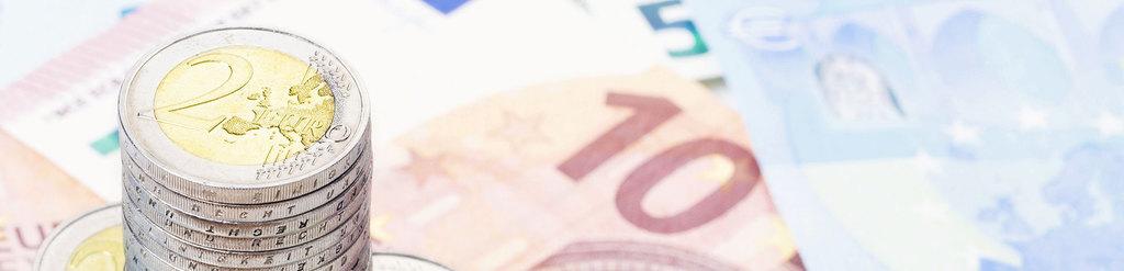 ein Stapel 2 Euro Münzen und im Hintergrund Geldscheine