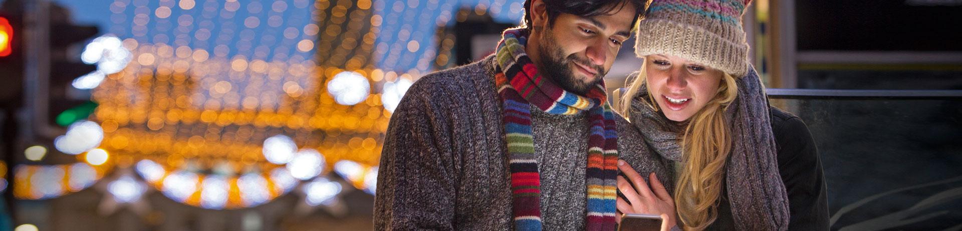 Ein Pärchen in weihnachtlicher Umgebung, das gemeinsam auf ein Handy blickt