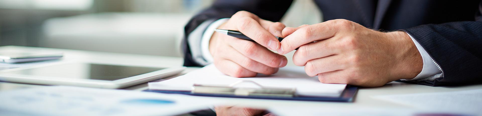 Ausschnitt von Händen mit einem Kugelschreiber in der Hand; davor liegen Papier und ein Tablet
