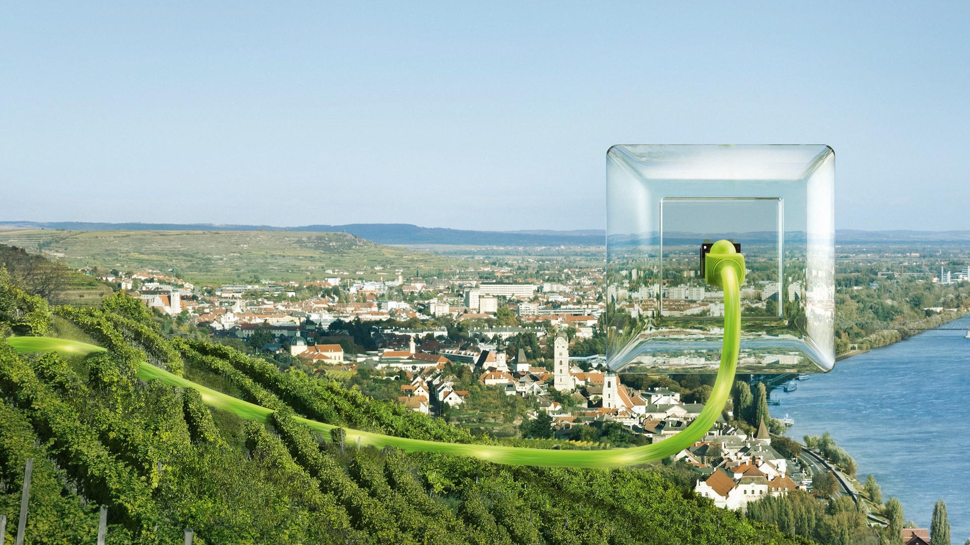 durchsichtige Steckdose mit einem grünen LAN-Kabel, das in das Stadtpanorama von Krems ragt.