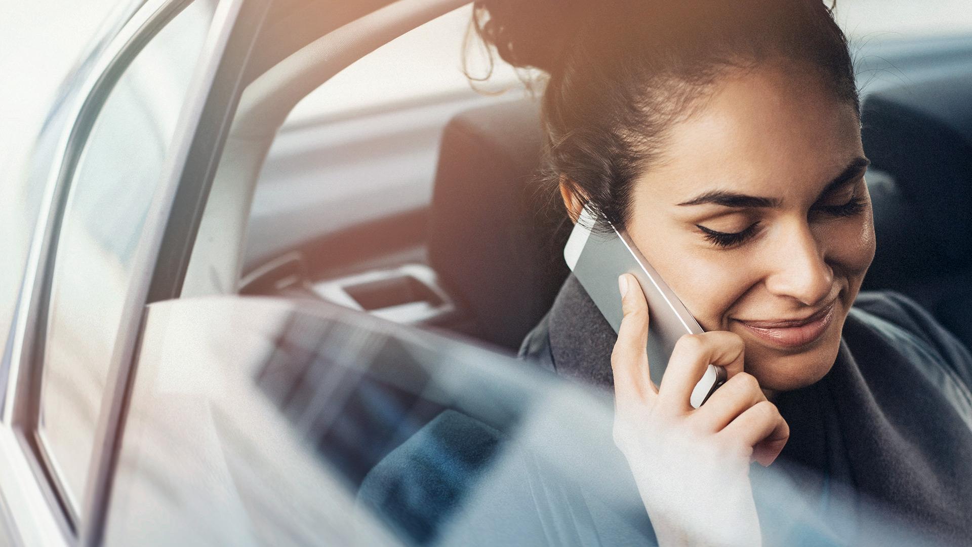 Junge Geschäftsfrau telefoniert im Auto.