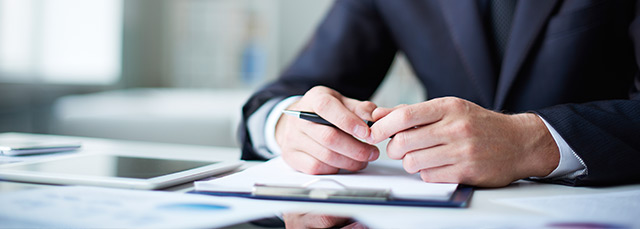 Hände, die einen Kugelschreiber halten, liegen auf einem Stapel Papier; daneben ein Tablet