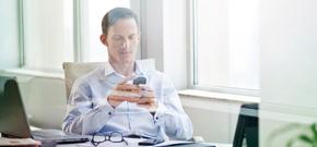 Geschäftsmann, der auf sein Handy schaut