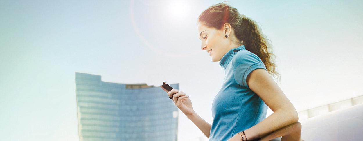 Dame steht im Freien und blickt auf ihr Handy; im Hintergrund ist ein großer Gebäudekomplex zu erkennen