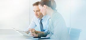 ein Mann und eine Frau arbeiten gemeinsam an einem Dokument