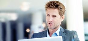 Junger Mann im Businessanzug sitzt vor dem Laptop