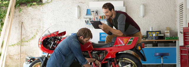 Zwei junge Männer arbeiten gemeinsam an einem Motorrad